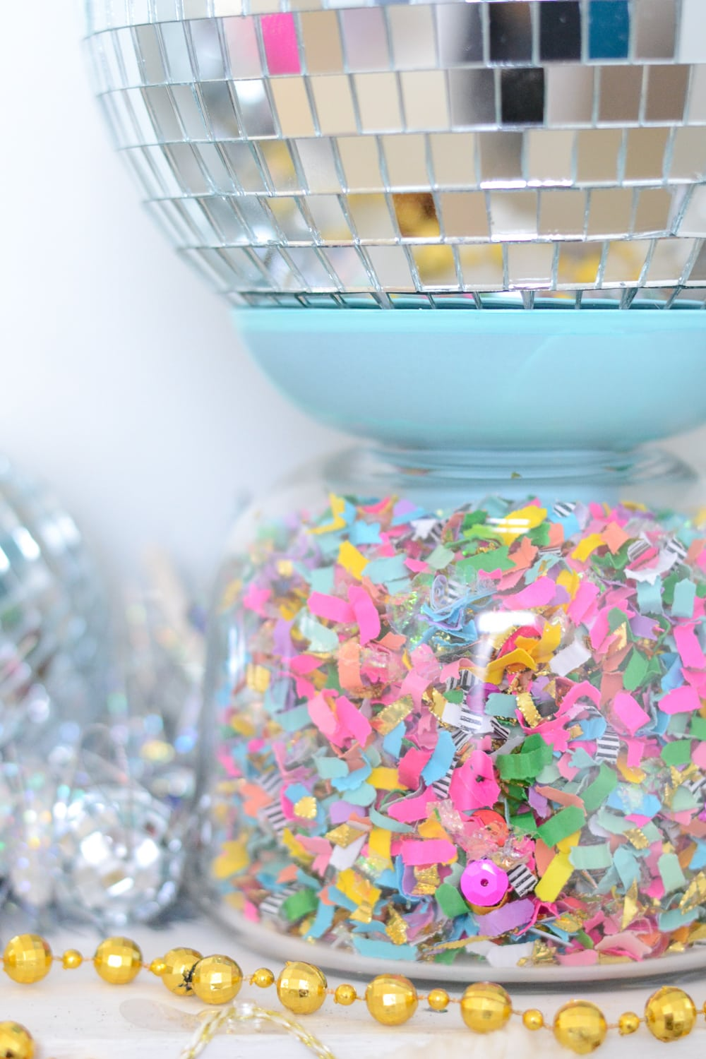 Revamp these IKEA vase candle holders by spray painting in bold colors and filling with confetti!